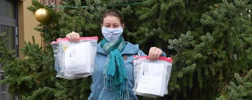 Frau mit Maske steht vor einem geschmückten Baum. In den Händen hält sie kleine Plastiktüten.