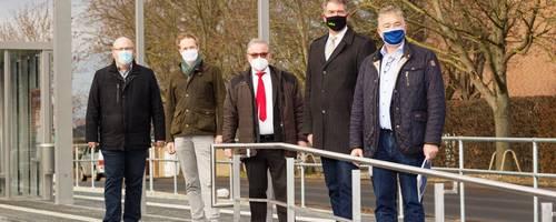 Fünf Männer stehen mit Masken auf einem Bahnsteig