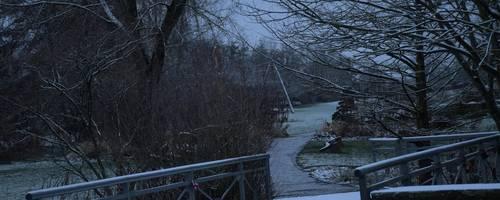 Brücke über die ein verschneiter Weg führt.