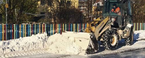 Ein Radlader lädt Schnee am Straßenrand auf seine Schaufel.