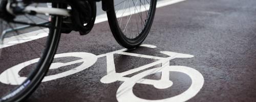 Ein Rad fährt auf einem markierten Fahrradstreifen.