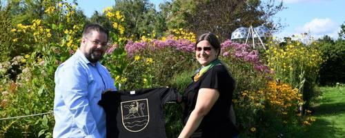 Zwei Personen, ein Mann und eine Frau stehen in einem Park. Hinter ihnen befindet sich ein buntes Blumenbeet. Sie halten ein schwarzes T-Shirt in die Höhe.