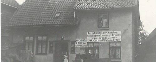Schwarz-Weiß-Foto eines Hauses mit Menschen und Kutsche vor dem Haus