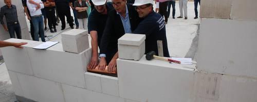 Ortsbrandmeister Thorsten Weinrich und Denis Schröder (links und rechts) legen die Grundsteinrolle in die vorbereitete Mauernische. [(c) Ilka Hanenkamp-Ley]