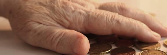 Hand, die nach Kleingeld auf einem Tisch greift