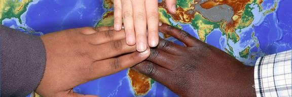 Drei Hände unterschiedlicher Hautfarbe halten sich über einer Weltkarte an den Händen