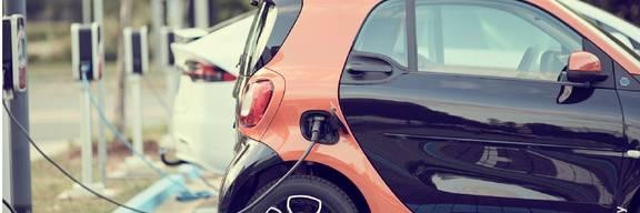 Ein Elektroauto steht an einer E-Tanksäule. Diese befindet sich auf einem Parkplatz.