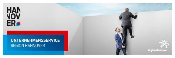 Logo der Region Hannover, der Wirtschaftsregion Hannover Zwei Männer welche mit Hilfer einer Räuberleiter eine Mauer überwinden