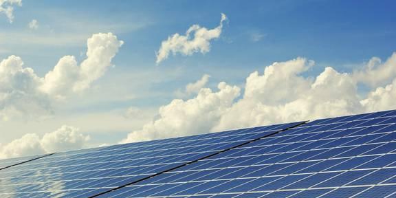 Solaranlage auf einem Hausdach, im Hintergrund Wolken am Himmel