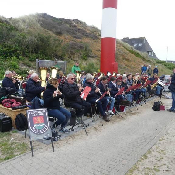 Orchester vor Dünen und Leuchtturm