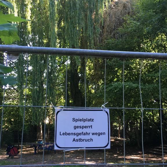 """Der Spielplatz ist mit Bauzäunen abgesperrt. Ein Schild warnt: """"Lebensgefahr wegen Astbruch"""""""