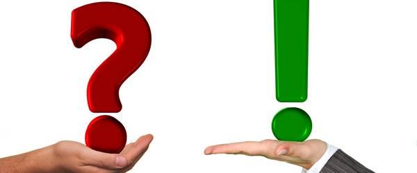 Fragezeichen und Ausrufezeichen auf einer Hand balanciert