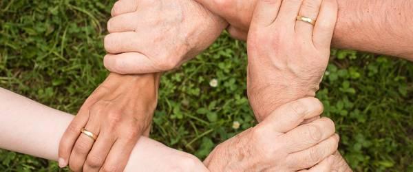 Hände einer Familie, die sich gegenseitig festhalten und einen Kreis bilden