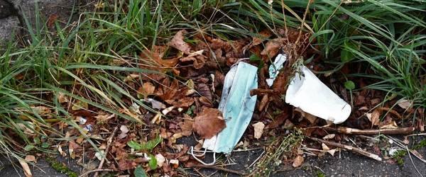 Eine Einwegmaske und ein Becher liegen im Gras. ©Katrin Förster
