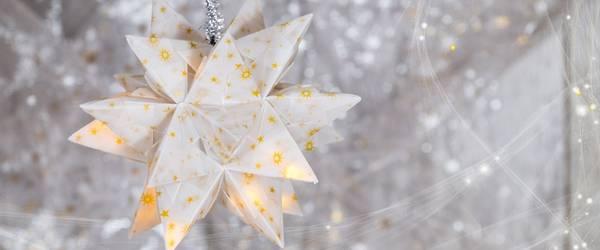 Weißer Stern, der aus vielen einzelnen Papieren gefatet ist und von innen leuchtet