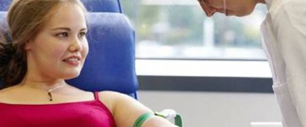 DRK Blutspendedienst nimmt Blut bei einer jungen Frau ab