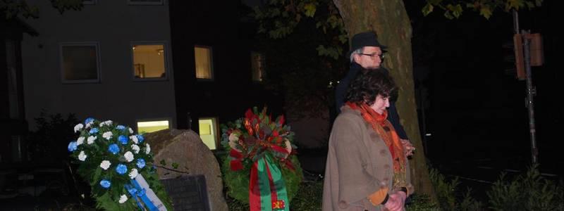 Zwei Menschen haben einen Kranz an einem Denkmal abgelegt
