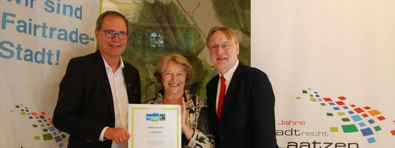 Bürgermeister Jürgen Köhne nimmt die Urkunde von Silvia Hesse (Fairtrade Deutschland) in Empfang. Mit dabei Bernd Lange (MdEP), Vorsitzender des Handelsausschusses des Europäischen Parlaments, [(c): Ilka Hanenkamp-Ley]