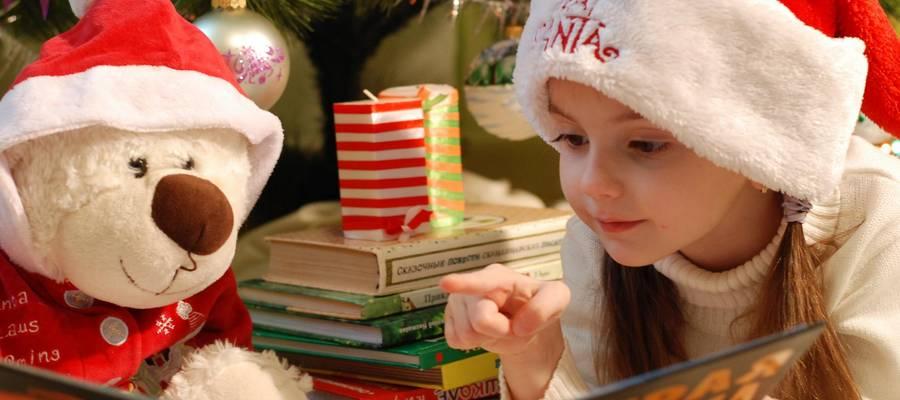 Mädchen mit Weihnachtsmütze liest ihrem Teddybären etwas vor