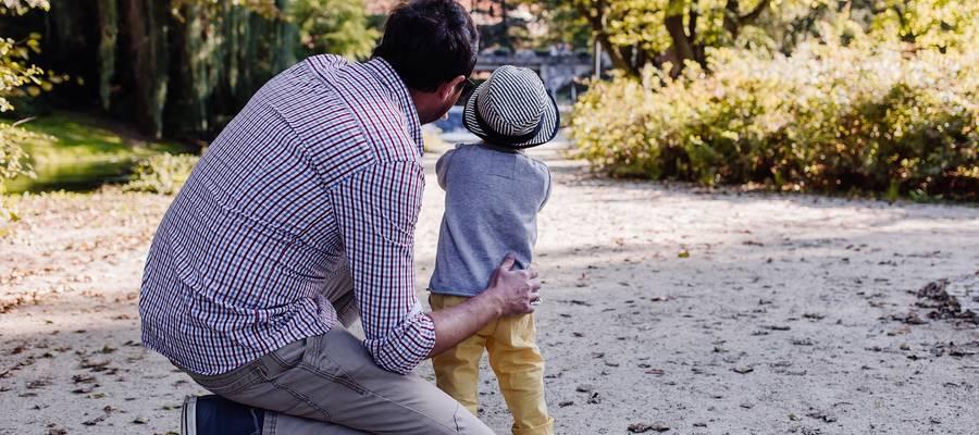 Vater kniet neben seinem Kind und spricht mit ihm