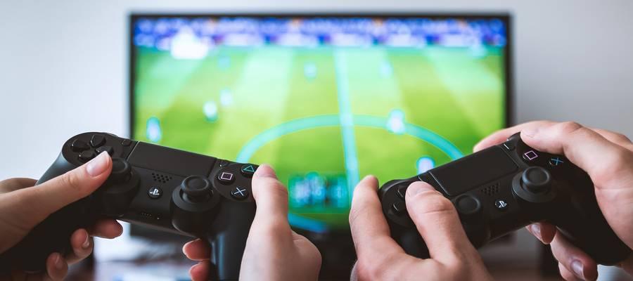 Zwei Hände mit Controller beim Fußball Game Spielen