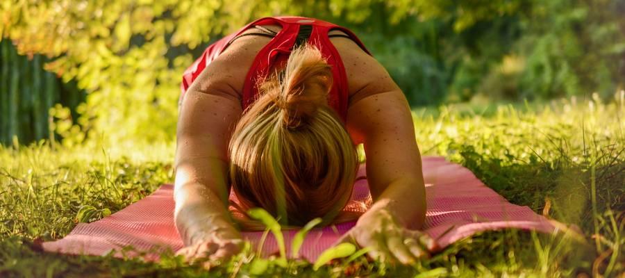 Frau macht Yogafigur auf einer grünen Wiese im Park