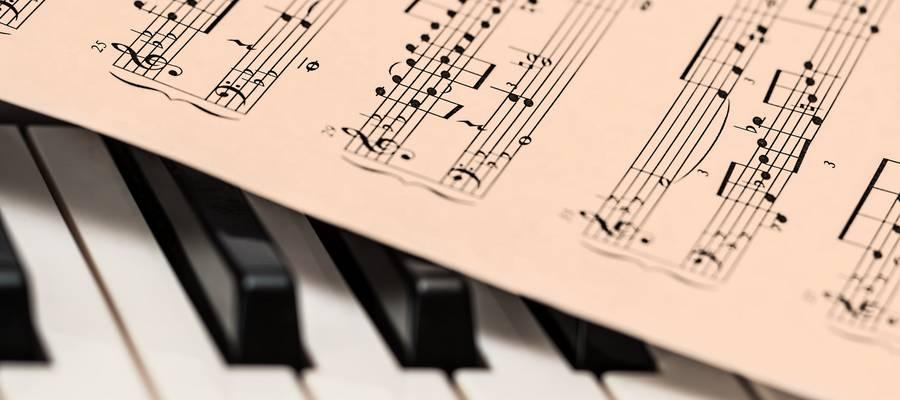 Notenblätter, die auf einer Tastatur liegen