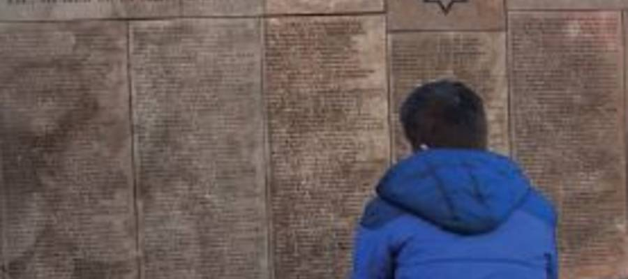 Junger Mann sitzt vor einer jüdischen Mauer