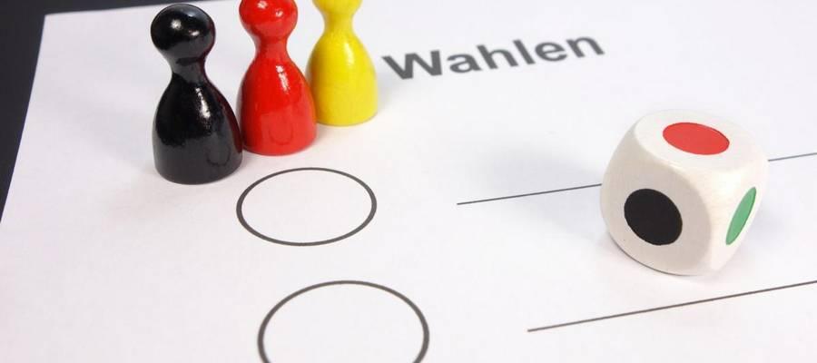 Wahlzettel mit drei Spielfiguren schwarz, rot, gold und Farb-Würfel