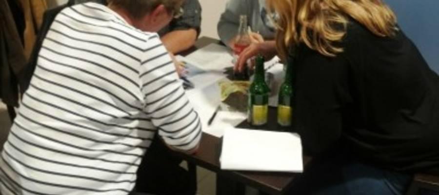 Vier Personen sitzen am Tisch und füllen die Tablequizbögen aus
